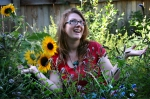 Jamie anointed with light. She is bathed with the sunflowers & mints in her urban garden.